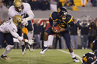 WVU quarterback Geno Smith avoids the Pitt pass rush. The WVU Mountaineers beat the Pitt Panthers 21-20 at Mountaineer Field in Morgantown, West Virginia on November 25, 2011.