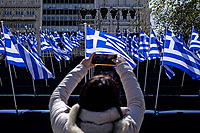Pictured: A woman takes a picture of the Greek flags in Syntagma Square, Athens, Greece. Wednesday 24 March 2021<br /> Re: Preparations are under way to celebrate the 200 anniversary from the beginning of the Greek revolution of 1821, after an almost 400 year rule by the Ottoman empire, Athens, Greece.