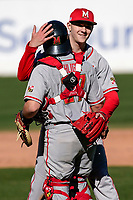 Freshman pitcher Jason Savacool (45) of the Maryland Terrapins, making his collegiate debut, pitched a complete-game 3-2 win against the Michigan State Spartans on Sunday, March 7, 2021, at Fluor Field at the West End in Greenville, South Carolina. Here he embraces catcher Luke Shliger (27) after the final out. (Tom Priddy/Four Seam Images)