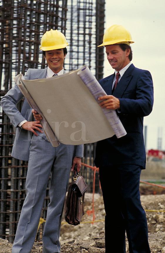 Businessmen review blueprints for commercial construction.