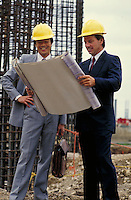 Businessmen review blueprints for commercial construction.