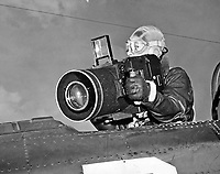 Students receiving familiarization with flight photography at Chevalier Field.  Student simulating operation of aerial oblique camera from open cockpit.