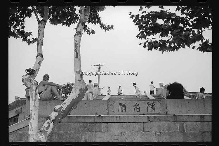 Local residents rest on Qingming Bridge over the ancient Beijing-Hangzhou Grand Canal in Wuxi, Jiangsu province, China, August 2013.