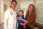 portrait of smiling Asian doctor and smiling woman holding infant