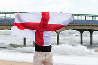 BNPS.co.uk (01202) 558833. <br /> Pic: CorinMesser/BNPS<br /> <br /> Pictured: Edd (Cor) King shows his support on a very windy Boscombe beach. <br /> <br /> England fans visiting the beaches of Bournemouth, Dorset show their support for the team ahead of the Euro 2020 semi-final against Denmark Tomorrow (Wed).
