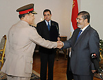 (FILE PHOTO: Former Armed Forces Chief of Staff Sami Anan shakes hands with former Egyptian President Mohammed Morsi at the Presidential Palace in Cairo, Egypt on Aug. 14, 2012 . Former President Mohamed Morsi died on Monday in court after the conclusion of a trial session in the espionage lawsuit, Egyptian state TV said. Photo by Egyptian Presidency