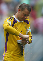 Germany goalkeeper Manuel Neuer wrings out his goalkeeping gloves at half time on a soaking wet afternoon in Recife