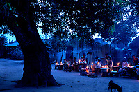 A market, illuminated by candle light, that takes place each night beneath a palavar tree. It is one of nine nearby villages that are off the electricity grid.