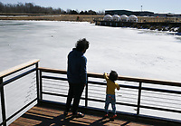 Dinesh Pirasingula of Bentonville (from left) and Dhrue Pirasingula, 3, look out onto a frozen over Lake Bentonville, February 22, 2021 in Bentonville. Check out nwaonline.com/210223Daily/ for today's photo gallery. <br /> (NWA Democrat-Gazette/Charlie Kaijo)