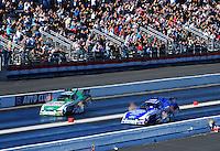 Feb. 27, 2011; Pomona, CA, USA; NHRA funny car driver John Force (left) races alongside teammate Robert Hight during the Winternationals at Auto Club Raceway at Pomona. Mandatory Credit: Mark J. Rebilas-.