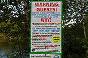 Warning signs at Staple Rock Park in Woodstock, New Hampshire during the summer months (COVID-19 pandemic). There has been an excessive amount of trash, human waste, and toilet paper being left at the town parks in Woodstock during the COVID-19 pandemic that the town had to post these signs warning visitors that the park would be closed if the behavior continued.