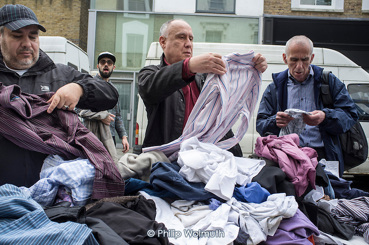 Men shopping for secondhand clothing on a stall in Portobello Road street market, London.