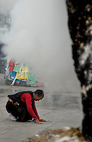 Images from the Book Journey Through Colour and Time,.The central part of Barkhor street is coverd in smoke, pilgrims burning their incense in giant Burners right in front of Jokhang Temple,Lhasa.The Jokhang Temple is one of Tibet's holiest shrines, originally built in 647 A.D. in celebration of the marriage of the Tang Princess Wencheng and the Tubo King Songtsen Gampo. In front of the gate is a stone Tablet of Unity from the Tang Dynasty; inscribed are both Chinese characters and Tibetan script. Nearby is the stump of the willow tree said to have been planted by Princess Wencheng herself; two younger willow trees now flank the stump of the first tree...Located in the center of old Lhasa, the temple was built by craftsmen from Tibet, China, and Nepal and thus features different architectural styles. The temple is also the spiritual center of Tibet and the holiest destination for all Tibetan Buddhist pilgrims. In the central hall is the Jokhang's oldest and most precious object--a gold statue of a seated 12-year-old Sakyamuni. This is said to have been transported to Tibet by Princess Wencheng from her home in Changan in 700 A.D. Other precious antiques in the temple include a silk portrait of Buddha from the Tang Dynasty and a pearl gown and gold lamp from the Ming Dynasty. The three-leafed roof of the Jokhang offers splendid views of the bustling Barkhor market and across to the Potala Palace..