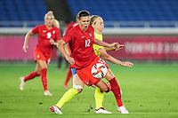 YOKOHAMA, JAPAN - AUGUST 6: Captain Christine Sinclair #12 of Canada gets fouled in the penalty box during a game between Canada and Sweden at International Stadium Yokohama on August 6, 2021 in Yokohama, Japan.