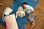 A child cries  as he lies in the dirt at the Chota Lahore refugee camp in Swabi district, Pakistan. Conditions in the camp are steadily worsening despite a third of the population leaving to return home with the Taliban being pushed back by the Pakistani army. Ration, wood, water and medical shortages are contributing to increasing frustration of the remaining residents and tensions are rising.