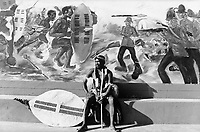A Zulu man rests below a mural depicting the battle scene of Isandlwana in Zululand. The mural is painted on a new school at the site of the Isandlwana battle near Pietermaritzburg.