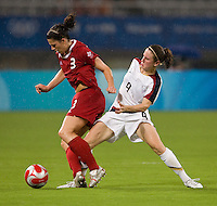 USWNT midfielder (9) Heather O'Reilly tries to take the ball away from  Canadian defender (3) Emily Zurrer while playing at Shanghai Stadium.  The US defeated Canada, 2-1, in extra time and advanced to the semifinals during the 2008 Beijing Olympics in Shanghai, China.