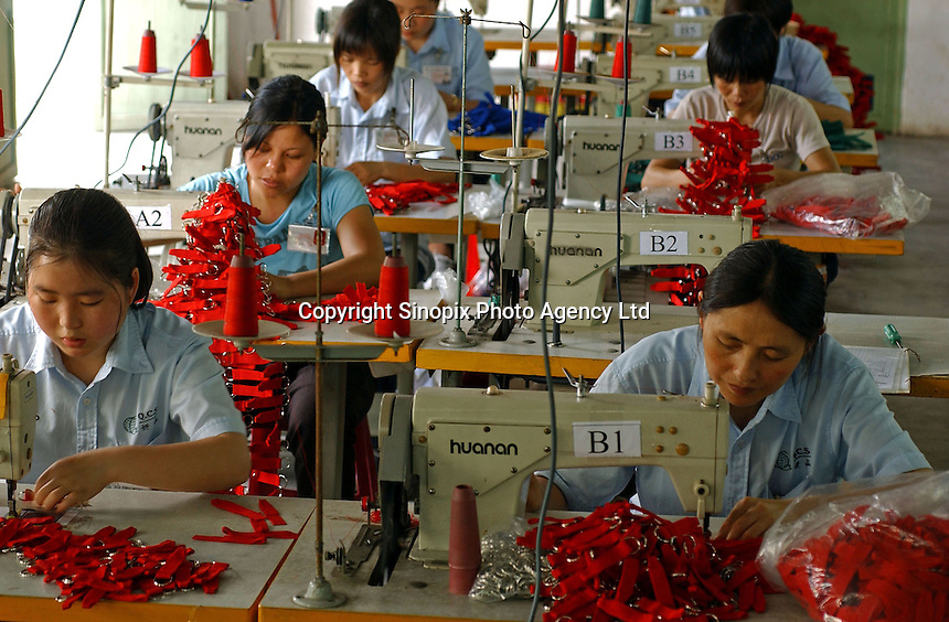 Workers on the production line of a factory in Zhouqing, Guangdong Province, China. The factory makes promotional gift items..06 May 2005