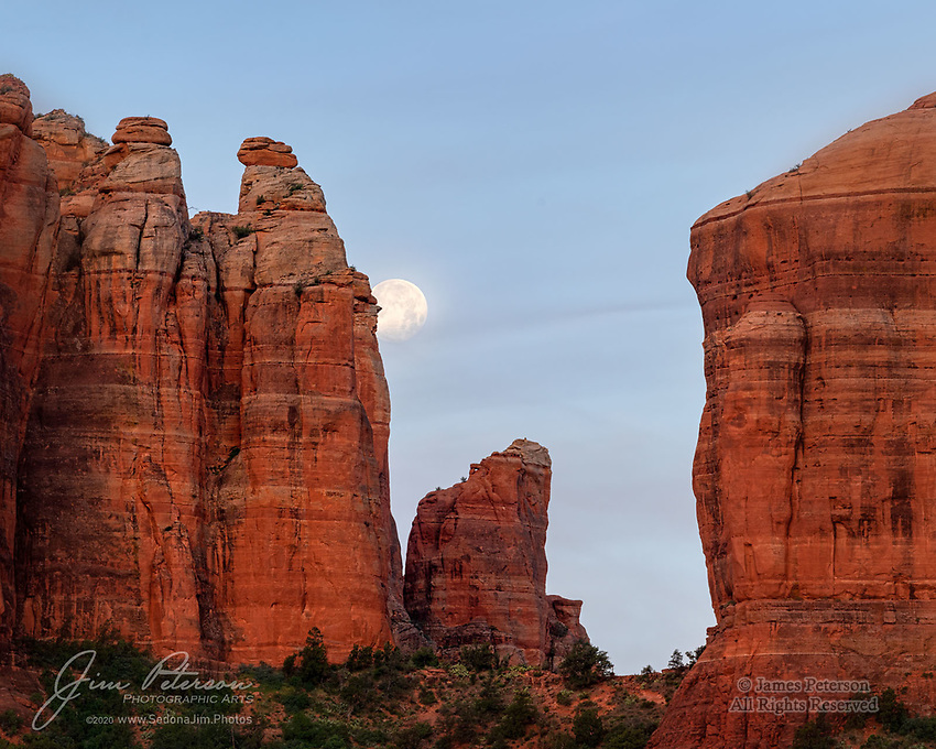 "Moonset over Cathedral Rock.  This was the last of the three ""supermoons"" of 2020, as seen just before sunrise on the day (May 8) after the full moon.  It was captured from atop a ridge overlooking the Templeton Trail in the Coconino National Forest, just south of Sedona.<br /> <br /> I thought at first that the thin clouds might ruin this photo, but I decided eventually that they actually add some nice character to the sky.  The glow of dawn above the eastern horizon added a nice bit of warmth to the red sandstone.<br /> <br /> Image ©2020 James D. Peterson"