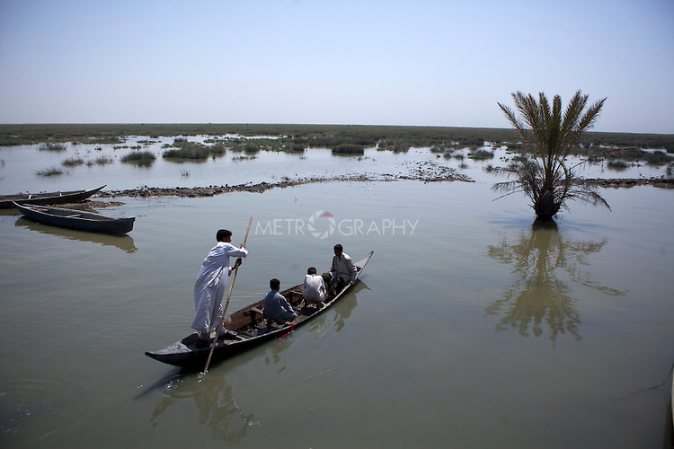 AL-SELKHA, IRAQ: A group of boys push their boat through the waterways around the village of Al Selkha...Dozens of families displaced by years of violence live in the village of Al Selkha in Nasiriya...Photo by Ali Arkady/Metrography