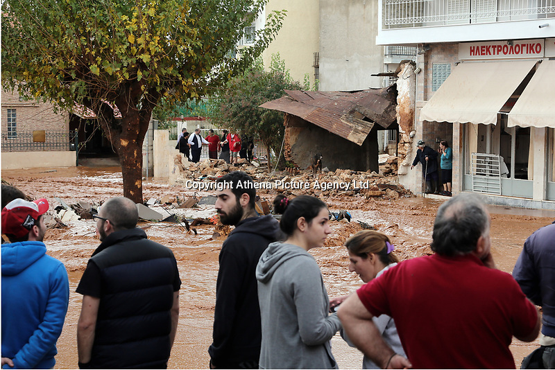 Pictured: Local people gather to assess the damage.<br /> Re: Five people have reportedly died and severe damage caused by heavy rain and flash flooding in the area of Mandra, near Athens, Greece. Wednesday 15 November 2017