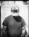 An Afghan interpreter, employed by the US military, is seen in Panjwayi, Kandahar 29 April 2013. This photograph was made using a 1950 Speed Graphic large format camera and a 1940 AeroEktar 2.5 lens, and has not been manipulated digitally. (John D McHugh)