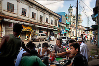 Burmese from various ethnic backgrounds eat breakfast near a mosque in Mawlamyine, Mon State. /Felix Features