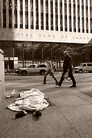 Pedestrians walk beside a homeless woman sleeping on the sidewalk facing  the Royal Bank of Canada building on King Street West in downtown Toronto, April 20, 2007.<br /> <br />     photo by Pierre Roussel - Images Distribution