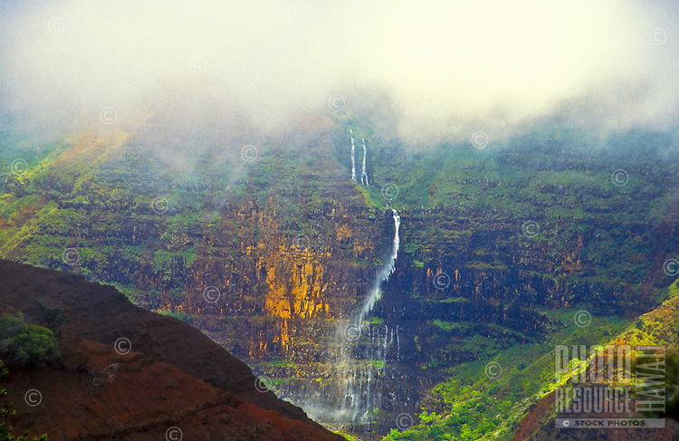 Clouds hug a waterfall cascading through Waimea Canyon, Kauai