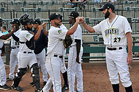 Starting pitcher Zac Grotz (15) of the Columbia Fireflies high-fives teammates before a game against the Charleston RiverDogs on Wednesday, August 29, 2018, at Spirit Communications Park in Columbia, South Carolina. Charleston won, 6-1. (Tom Priddy/Four Seam Images)