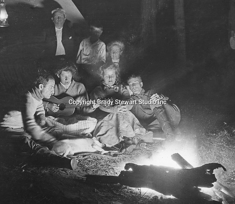 North East PA: Aunt Maggie leading the Stewart family in song around the campfire.  Brady Stewart is throwing flash power on the campfire to create an image.  During the early 1900s, the Stewart family vacationed on Lake Erie near North East Pennsylvania. Since hotels and motels were non-existent, camping was the only viable option for a large number of vacationers.