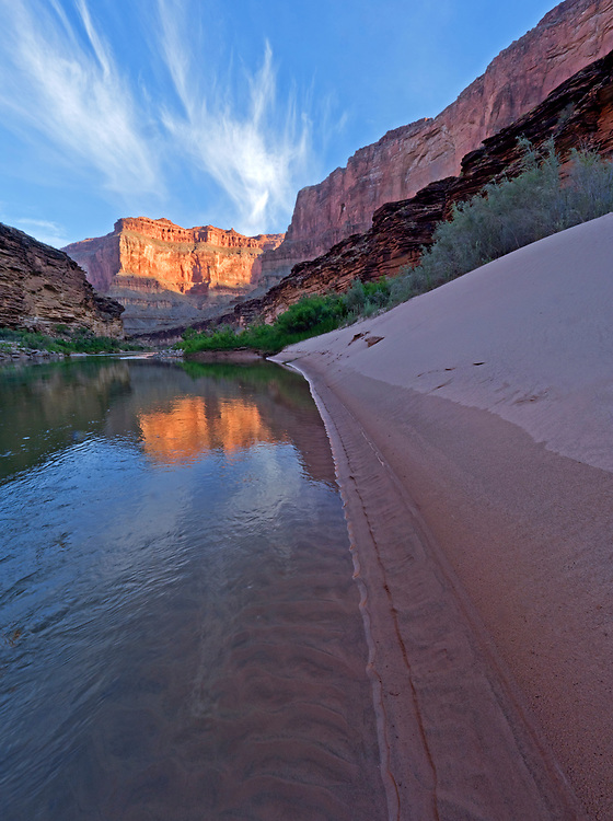 The rising sun illuminates distant cliffs viewed from 119.8 Mile Right camp along the Colorado River in the Grand Canyon, Grand Canyon National Park, Arizona, USA