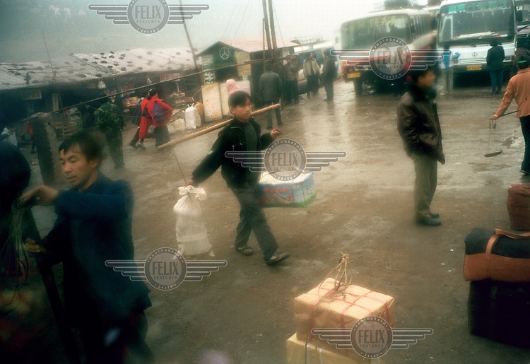 A migrant worker carries the belongings of passengers boarding buses to relocate to the new city further up the hill.  Residents of the old part of the city are being relocated in order to make way for the Three Gorges Dam project, which will raise the water levels of the Yangtze river and inundate lower-lying areas.