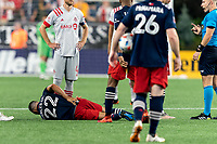 FOXBOROUGH, MA - JULY 7: Carles Gil #22 of New England Revolution absorbs another hit during a game between Toronto FC and New England Revolution at Gillette Stadium on July 7, 2021 in Foxborough, Massachusetts.
