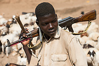 ETHIOPIA, Southern Nations, Lower Omo valley, Kangaten, village Kakuta, Nyangatom tribe, shepherds give water to their goats from water holes at dry river Kibish, the shepherds carry Kalashnikov AK-47 machine guns to protect themselves from cattle raids of hostile Turkana tribe / AETHIOPIEN, Omo Tal, Kangaten, Dorf Kakuta, Nyangatom Hirtenvolk, Hirten traenken das Vieh aus Wasserloechern am trocknen Fluss Kibish, die Hirten tragen Kalaschnikow AK-47 Maschinengewehre zum Schutz vor Viehdiebstaehlen durch Turkana Voelker