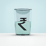Glass half full with rupee symbol representing hope of currency growth