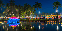 Colorful Loy Krathong festival decoration, lamp, and palm tree reflections on the lake at night in the famous Sukhothai Historical Park, Thailand