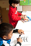 Education preschool 3-4 year olds boy practicing tracing his name with dry erase marker as boy next to him plays with puzzle