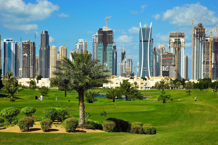 Dubai.  Skyline of Emirates Lakes Towers, Jumeirah Beach Residences and Dubai Marina   overlooks the Montgomerie Golf Course at Emirates Hills.  Villa developments..