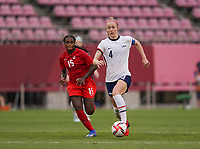 KASHIMA, JAPAN - AUGUST 2: Becky Sauerbrunn #4 of the United States dribbles the ball in front of Nichelle Prince #15 of Canada during a game between Canada and USWNT at Kashima Soccer Stadium on August 2, 2021 in Kashima, Japan.