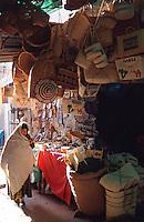 Tunisia Gabes A woman walking through an alley of basket vendors