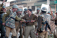 Local police officer being beaten by federal paramilitary police apparently for refusing the paramilitary into the property he was guarding. This happened during confrontation with  stone throwing youth following Friday prayer at the Jamia Masjid mosque.  Srinagar, Kashmir, India.  Fredrik Naumann/Felix Features