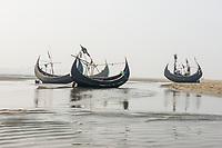 Bangladesh, Cox's Bazar Beach.The longest unbroken sea beach in the world running 75 miles. Moon shaped fishing boats docked on the beach.