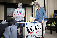 League of Women Voters members Kay Abney (from left) and Margaret Gilmore prepare their materials to help register people to vote, Friday, September 11, 2020 at the Springdale Senior Center in Springdale. The senior center hosted a food drive by the Northwest Arkansas Food Bank. They handed out enough food for 310 families. The food bank distributes at the site every second Friday of the month, but they will move their mobile pantry to Parson's Arena starting October. In addition, members of the League of Women Voters also helped register people to vote and reminded them to complete the census. Check out nwaonline.com/200912Daily/ for today's photo gallery. <br /> (NWA Democrat-Gazette/Charlie Kaijo)