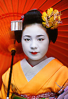 "Kyoto, Japan. Komomo, a maiko with umbrella.   This girl is an apprentice maiko, Komomo or ""little peach,"" in training with her onee-san ""older sister."" Yachiho-san is a fully trained geisha, or geiko as Kyoto's geisha are known. I was invited to enter the mysterious world of these artisans and access some private time with the girls as they prepared for their evening."