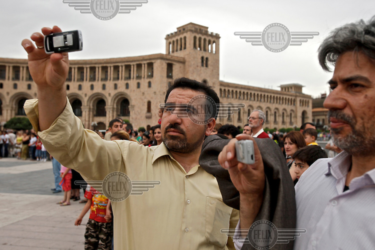 Two male tourists use their mobile phones to take pictures in Yerevan, the capital of Armenia.