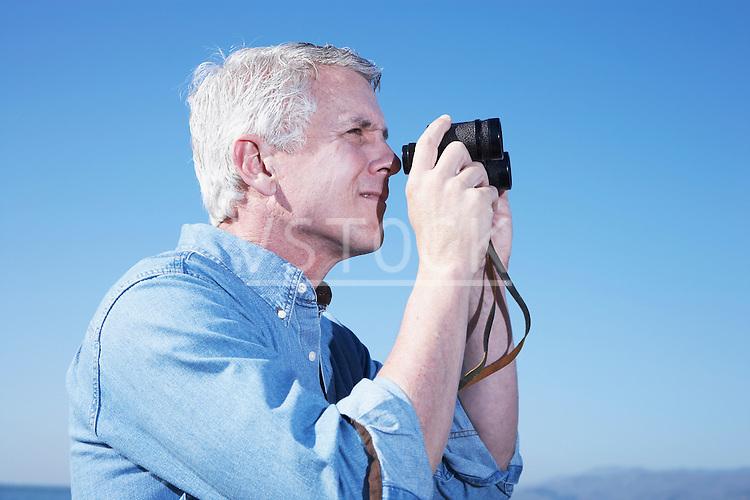 USA, California, Fairfax, Mature man looking through binoculars against blue sky