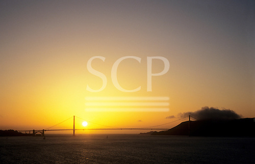 San Francisco, USA. View across bay at dusk to Golden Gate Bridge silhouetted against setting sun and orange sky.