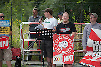 """29 Neonazis von NPD und Autonomen Nationalisten aus Berlin und Brandenburg protestieren in Berlin-Weissensee gegen eine geplante Fluechtlingsunterkunft.<br /> Aufgrund einer Auflage der Polizei durften sie nicht vor dem Gebaeude stehen, sondern mussten einige Meter weiter vor einem Brachgelaende Aufstellung nehmen.<br /> Ca. 100 Menschen protestierten gegen die Neonazi-Kundgebung.<br /> Im Bild: Der Neonaziaktivist Christian Schmidt redet zu seinen Kameraden.<br /> Rechts neben Schmit NPD-Schild: Romano Subke, Neonazi aus Hellersdorf, mit T-Shirt """"Weisse Woelfe Terrormachine"""".<br /> 9.8.2014, Berlin<br /> Copyright: Christian-Ditsch.de<br /> [Inhaltsveraendernde Manipulation des Fotos nur nach ausdruecklicher Genehmigung des Fotografen. Vereinbarungen ueber Abtretung von Persoenlichkeitsrechten/Model Release der abgebildeten Person/Personen liegen nicht vor. NO MODEL RELEASE! Don't publish without copyright Christian-Ditsch.de, Veroeffentlichung nur mit Fotografennennung, sowie gegen Honorar, MwSt. und Beleg. Konto: I N G - D i B a, IBAN DE58500105175400192269, BIC INGDDEFFXXX, Kontakt: post@christian-ditsch.de<br /> Urhebervermerk wird gemaess Paragraph 13 UHG verlangt.]"""