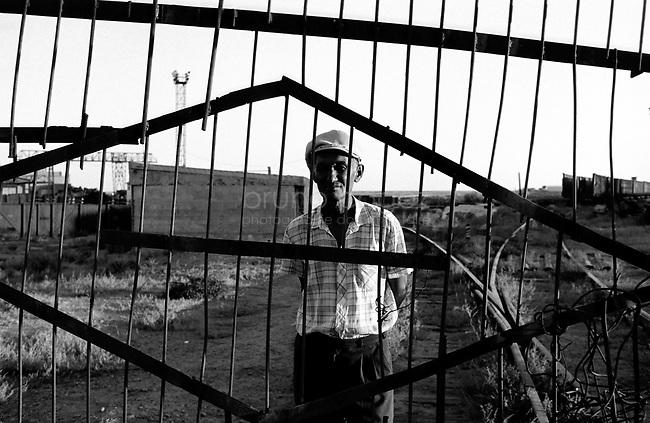 KAZAKHSTAN, Aralskoe More, 2001..A month in Kazakhstan, lookng for the Aral sea..A guard at the former railway terminal of the old port. Aralskoe more was the main port until the sea withdrew several kilometers..KAZAKHSTAN, Aalskoe More, 2001..Un mois au Kazakhstan à chercher la mer d'Aral..Un gardien devant la grille de l'ancien terminal ferroviaire du vieux port. Aralskoe More était le principal port sur la mer d'Aral avant qu'elle ne se retire de plusieurs kilomètres..© Bruno Cogez.